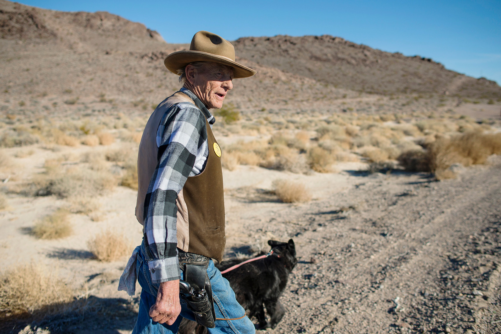Rugged cowboy walking across the desert with his dog